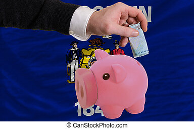 Man putting euro into piggy rich bank and flag of us state...
