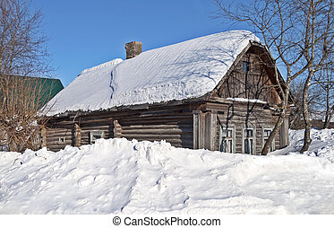 Old log hut covered with snow