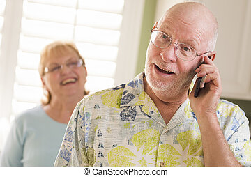 Senior Adult Husband on Cell Phone with Wife Behind - Happy...