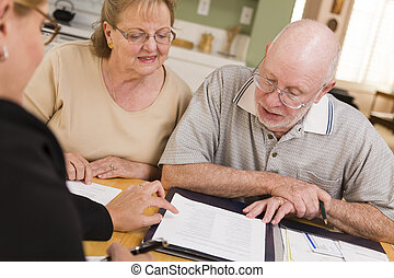 Senior Adult Couple Going Over Papers in Their Home with...