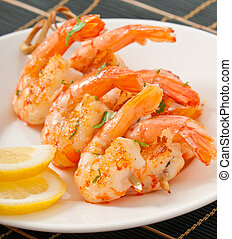 Fresh grilled shrimps with lemon on white plate