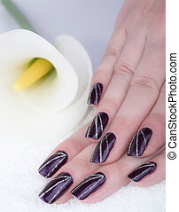 Woman with beautifully manicured purple nails with cala lily