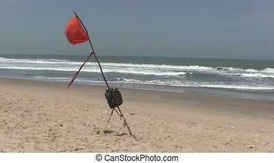 Red warning flag - Red warning flag flying on a deserted...