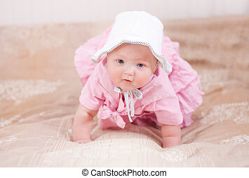 Cute baby in pink dress - Lying on a bed