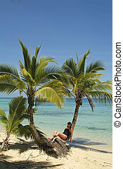 Fiji - Fiji, woman relaxing between coco palm trees on a...
