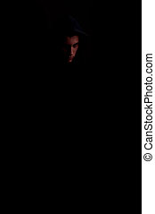 face of a young man in the dark