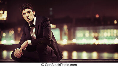 Stylish man with night town over the background - Stylish...