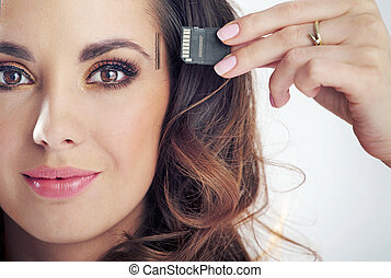 Young smiling woman inserting card into her head - Young...