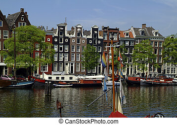 Netherlands, Amsterdam, Amstel river with boats and homes...