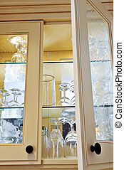 Kitchen cabinet close up with glass shelves and glasses