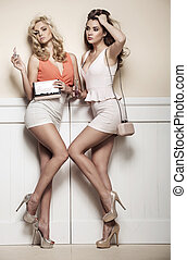 Adorable girlfriends posing against to the wall - Adorable...