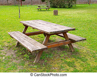 Table and benchs in a park. An outdoor scene.