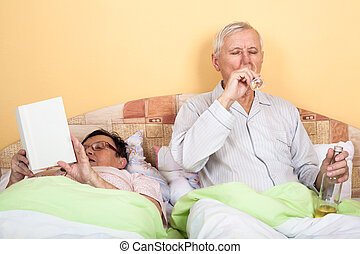 Seniors relax with alcohol in bed