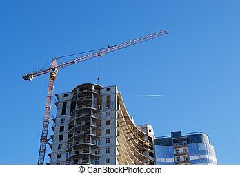 Construction crane on the background of a skyscraper under construction, and the sky with vapor trail from an airplane