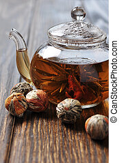 Chineas flowering tea in glass teapot on wooden background