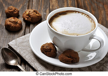Cup of coffee with cookies over wooden background