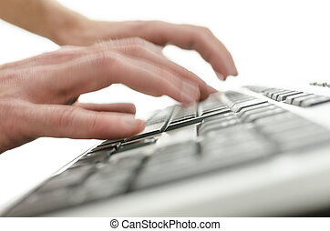 Blurred hands typing on computer keyboard
