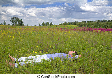 Man lying on a spring meadow - Happy young man lying on...