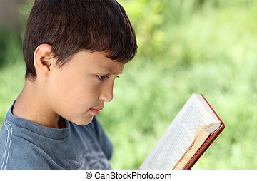 Young boy reading book outside with natural green background...