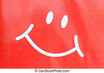 Smiley face symbol on plastic background
