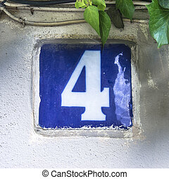 Nr 4 - glazed house number four, next ot some green leafs