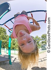 girl on monkey bars - Young girl hanging upside down from...