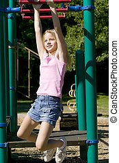 Girl on monkey bars - Young girl swinging from monkey bars