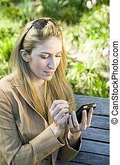 Blond woman using PDA