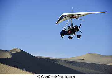 powered glider flying above the desert