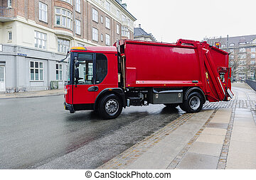 Red garbage disposal truck parked at the side of a street...