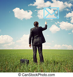businessman standing in the field and points a finger at mail