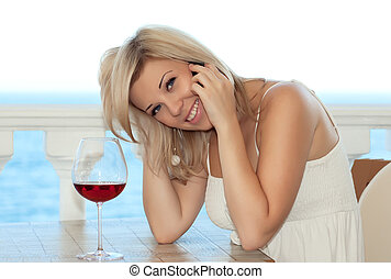 Beautiful girl talking on the phone in a cafe and drink wine