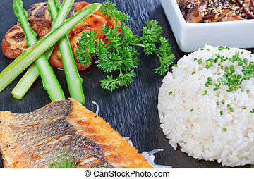 A delicious piece of fish on a background of greens, rice...