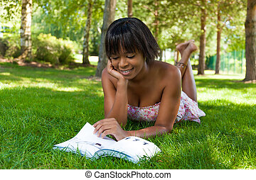 Outdoor portrait of young black woman reading a book