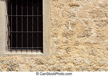 Window with grille - Fragment of old stone wall with window...