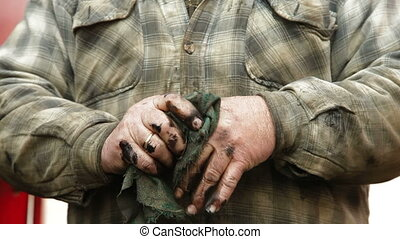 Dirty hands of auto mechanic - Auto mechanic wipes his dirty...