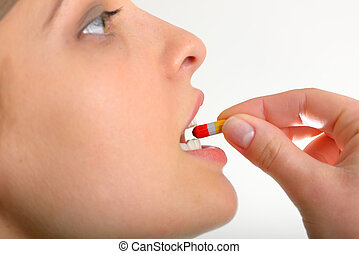 Woman taking pills - close-up young woman on studio isolated...