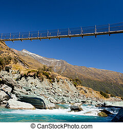 Swing bridge high over glacial river New Zealand - Simple...