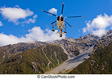 Rescue helicopter fly over mountainous wilderness - Small...