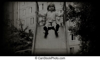 Children spending time in playground slide. Vintage 8 mm...