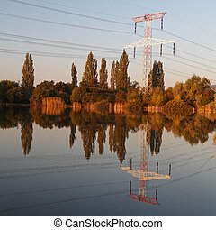 Electricity pylon with reflection in water at sunset
