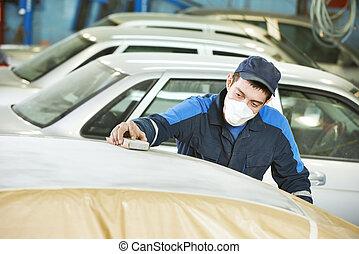 repairman sanding automobile roof - professional repairman...