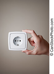 Hand with electric outlet - Hand holding an electric outlet