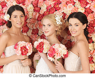 three women with background full of roses - beautiful three...