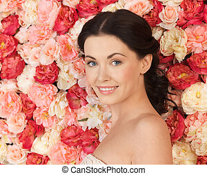 woman with background full of roses - portrait of beautiful...