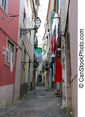 Cobblestone Alfama street with laundry hanging - Narrow...