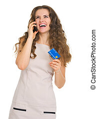 Happy young woman with credit card talking mobile phone