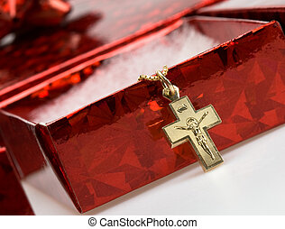 Red gift box with baptismal cross draped over it Cross has...
