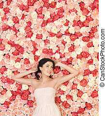 young woman with background full of roses - beautiful and...