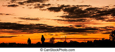 Two silhouettes walking in the sunset